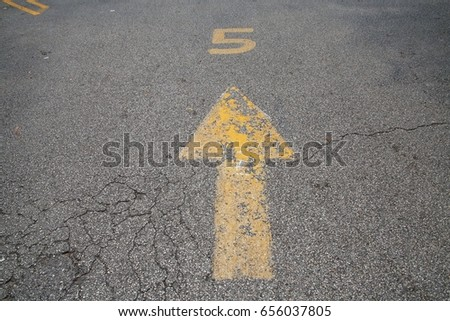Yellow Arrow with Number 5 Above Painted on Parking Lot Pavement #656037805