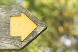 Yellow arrow within a wooden signpost pointing to a direction