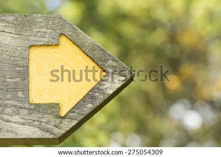 yellow arrow within a wooden...