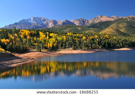 Yellow Aspen leaves being reflected at the scenic Crystal Reservoir in the Pike National Forest, of Colorado, during the autumn season with Pikes Peak soaring above