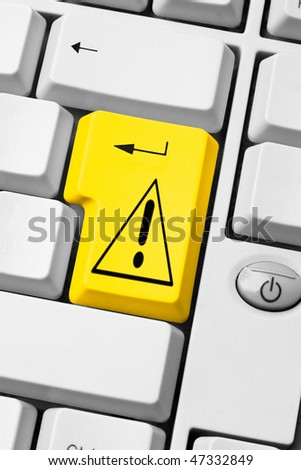 yellow attention symbol on enter key computer keyboard, web navigation alert, danger on internet