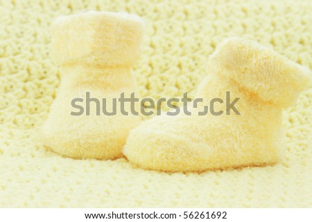 Yellow baby booties and blanket with room for text.