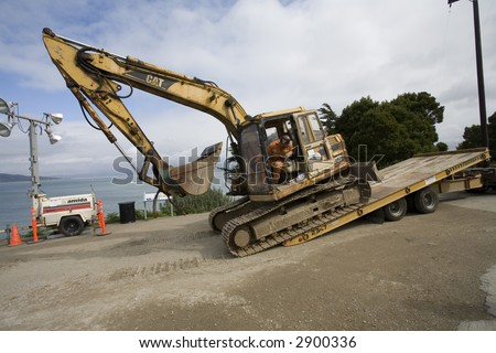 Yellow Backhoe Loading on Flatbed Truck