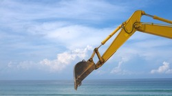 Yellow backhoe with hydraulic piston arm against blue sky. Heavy machine for excavation in construction site. Hydraulic machinery. Huge bulldozer. Heavy machine industry. Mechanical engineering.