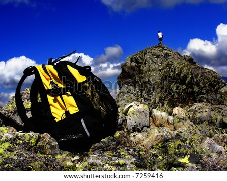yellow backpack on top of the mountain