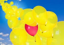 Yellow balloons with one red in sunny sky