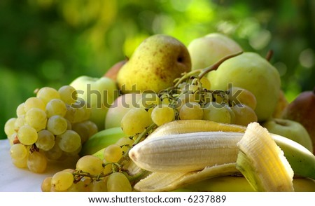 Yellow banana and green apple on green background