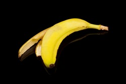 Yellow banana peel waste isolated on the black background