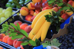 Yellow bananas and fruits on a market counter
