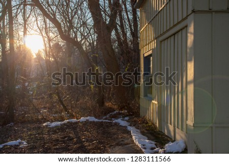 Yellow barn and woods with the sun setting and snow on the ground in New Jersey