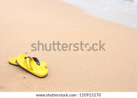 Yellow beach slippers on sandy beach, summer, bathing