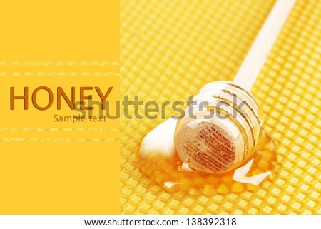 Yellow beautiful honeycomb and wooden honey dipper with honey