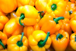 yellow bell peppers with bright green ponytails closeup background