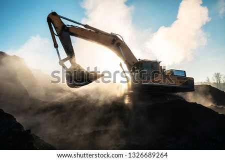 Yellow big excavator in the coal mine, loads the breed, with the bright sun and nice blue sky in the background. Mining truck mining machinery. Technique in coal mine