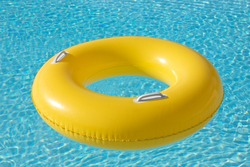 Yellow big float on pool with a blue water ready to swim