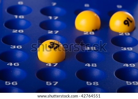 Yellow Bingo balls placed in the slots on a blue board - stock photo