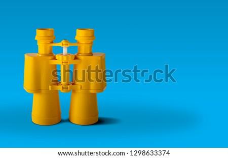 Yellow binoculars isolated on blue background #1298633374