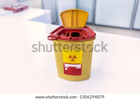 Yellow biohazard medical contaminated sharps clinical waste container isolated on white background.