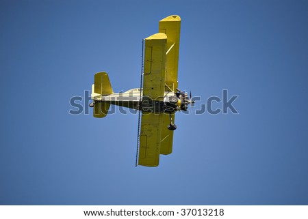 Yellow biplane, crop duster, flying against the blue sky.