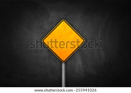 Yellow blank road sign on black wall