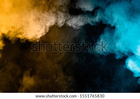 Yellow blue powder explosion cloud on black background. Freeze motion of color dust  particles splashing.
