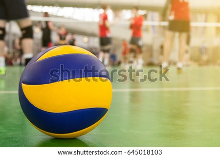 Yellow-blue volleyball on the floor in the gym, team of athletes playing volleyball
