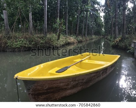 Yellow boat and paddle float in channel at green tree garden #705842860