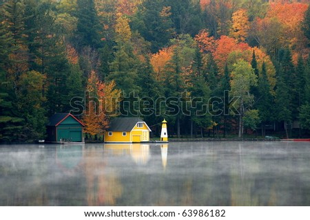 Yellow boathouse sits along the shore surrounded by the beauty of autumn/Yellow Boathouse/Autumn's colors highlight the beauty of the landscape.