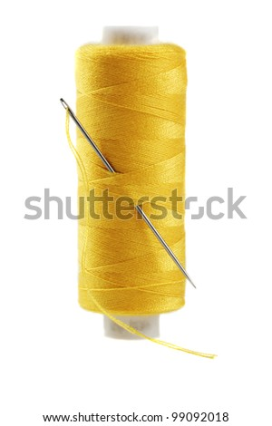 Yellow bobbin of thread with needle isolated on white