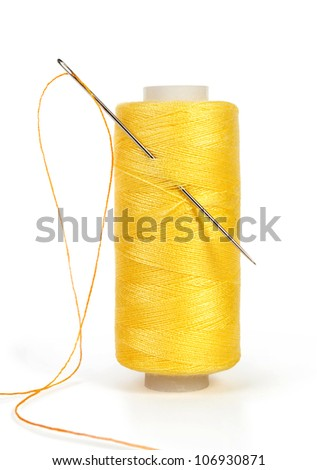 yellow bobbin thread with needle and sewing pin isolated on white