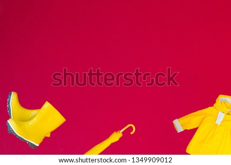 yellow boots, yellow umbrella, yellow raincoat on an isolated red background