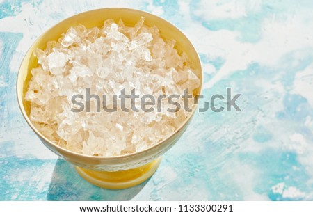Yellow bowl of crushed clean ice for use as an ingredient in cooking or beverages over a cool mottled blue background with copy space
