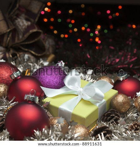 yellow box tied with a white ribbon and christmas decoration - stock photo