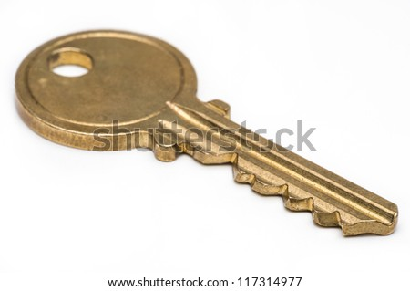 Yellow brass key on isolated white background. - stock photo