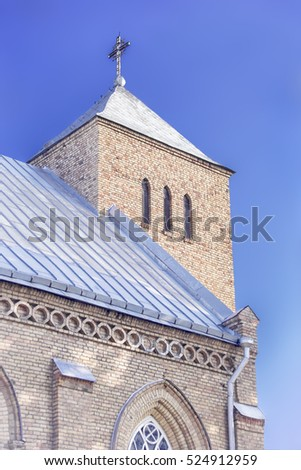 Yellow brick church tower with cross in Vepriai, Lithuania