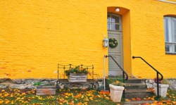 Yellow brick house entrance with seasonal wreath on door and porch window on autumn day with fall leaves on the ground. Iron bench furniture and wooden box garden flowers - vintage autumn decoration