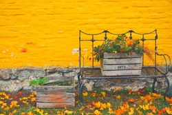 Yellow brick house on autumn day with fall leaves on the ground. Iron metal bench furniture and wooden box garden flowers - vintage autumn season decoration. October foliage, rustic exterior decor
