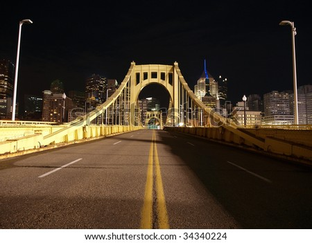 Yellow bridge leading to downtown Pittsburgh.  Lit with the glow of baseball stadium lights.