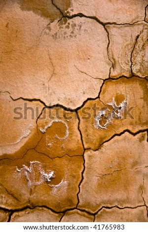 Yellow, brown and white scorched earth abstract background with multiple cracks and stains.
