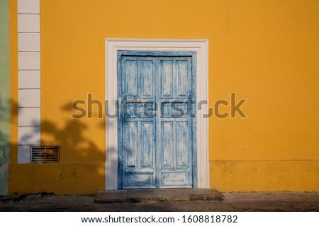 Yellow building with blue door in Merida, Yucatan