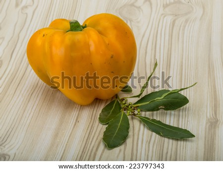 Yellow Bulgarian Pepper with laurel leaves on the wood background