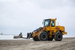 Yellow bulldozer excavating sand on dutch beach working. Clouded weather seashore netherlands. Heavy work equipment.