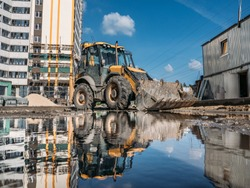Yellow bulldozer excavator with bucket on construction site with new building on background and reflection in puddle water.