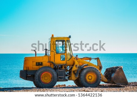 Yellow bulldozer on the background of clear blue sky and sea. Copy space. Copy space and close up.