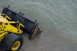 Yellow bulldozer with a wheel drive lowering black metal blade, drove into the sea in the coastal zone of shallow water. Concept: Using heavy construction equipment to improve and update beach area.