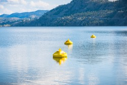 Yellow buoys marking hazardous area with dangerous under currents on lake, where swimming is not permitted