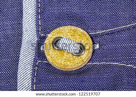 Yellow button on jeans texture close view