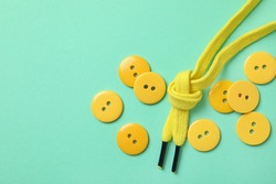 Yellow buttons and shoelaces on mint background