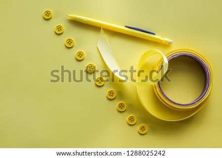Yellow buttons, yellow bow and yellow pencil on yellow background table top