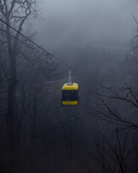 Yellow cabin lift in the fog. Mystic atmosphere, foggy weather. Chairlift moving on cable. Beautiful view, forest during the fall season. Breathtaking background.